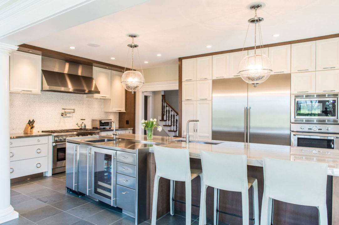Decora cabinetry with Coriander Espresso Stain and Chantille paint finish with Autore Metal Ring Pulls by Richelieu and Contemporary Metal Handle Pulls from Richelieu. Macaubus Quartz with mitered edge and custom stainless countertops.