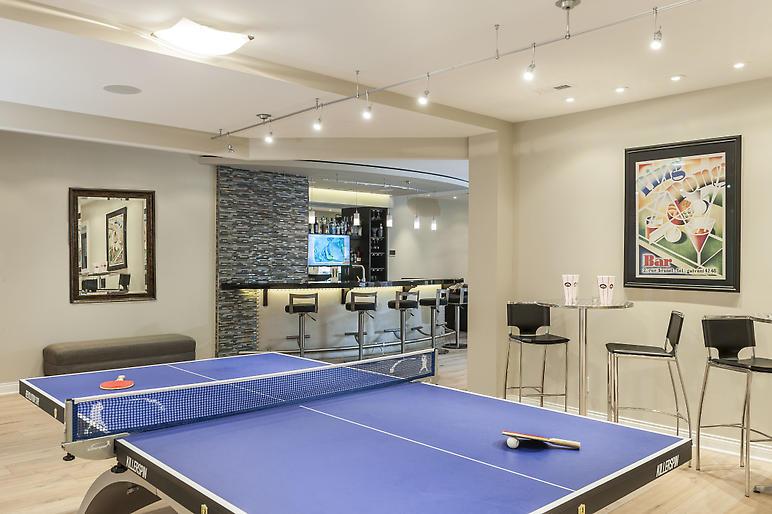 basement bar, quartz counters, wood bar top, pendant lighting, mirrored backsplash, curved bar, game area