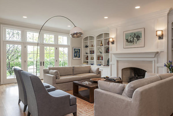 Elegant family room grey and cream with floor to ceiling windows and patio doors, white custom built in cabinets
