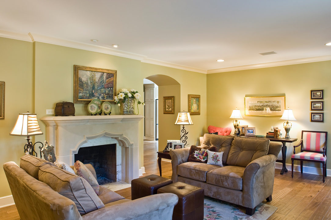 limestonefireplace with marble surround, arched opening into kitchen, relocated front door to open up floor plan