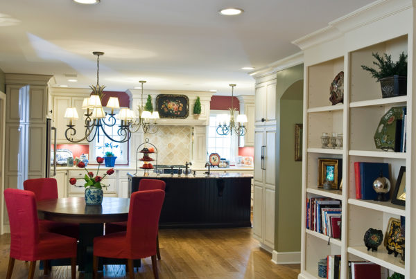 emperador marble island with dual chandeliers, complementary two-toned cabinets, custom built-ins