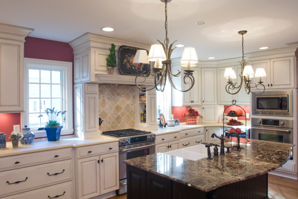 emperador marble island with dual chandeliers, complementary two-toned cabinets, under mount farm sink, custom built-ins