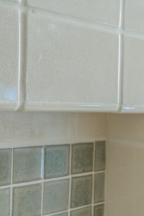 glass tile backsplash in linen closet area