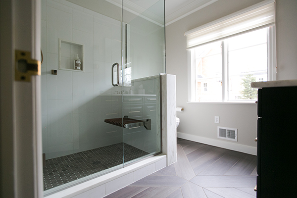 Basketweave tile floor, bronze cassidy shower fixtures, flip up shower seat, gray basket weave with calcutta mosaic, shower with knee wall, gray and white shower