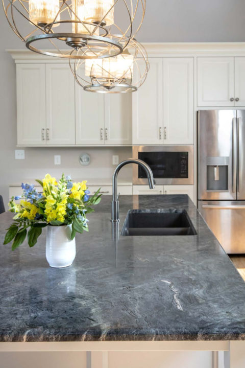 Kitchen island Capital Medium Rivier Pendants, GE Appliances (built in dishwasher and counter depth fridge), stainless appliances,GE Profile Built in microwave, Maple Custom Cabinetry with Neutral Ground Painted finish on perimeter and Osprey on Island, Amerock Crawford Knobs and Pulls, painted kitchen cabinetry, white cabinetry, Phoenix Quartzite with half bullnose edge on island and Vicostone Akoya Quartz with no splash on perimeter, quartz countertops, quartzite counters