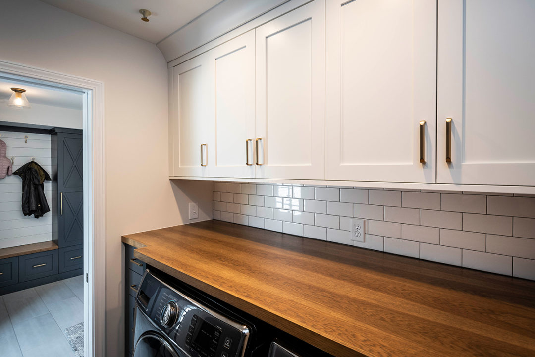 "3x6 Ice White Tile, white tile in brick pattern with black grout, wall tile patterns, blue and white laundry room, blue cabinetry with gold hardware, 1-1/2"" Wood Countertop, Maple Shaker Door cabinets with Pure White Paint uppers and Sea Serpent Painted lowers"