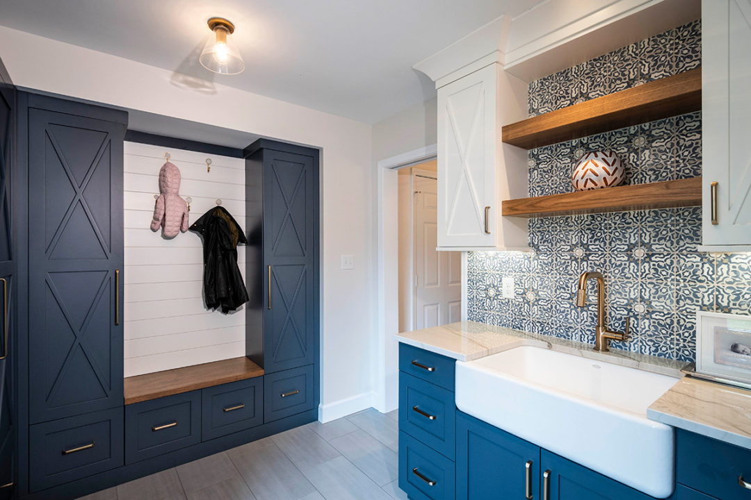 "Fun Mudroom with Family Lockers, Blue and Gold Mudroom, blue and white mudroom, Whitehaven 30"" Single Basin Apron Front Sink, Litze Pull Down Faucet by Delta in Champagne Bronze, Walker Zanger Duquesa tile in the color Fatima Mezzanotte, Unique square tile pattern, cement tile, Calacatta Basil Quartzite counter, wood bench, Maple custom cabinetry with Shaker Doors with custom ""X"" doorstyle, wall cabinets and Ship lap Pure White Paint and Tall and Base Cabinets Sea Serpent Paint, Floating Wood Shelves stained in Hickory Cafe"