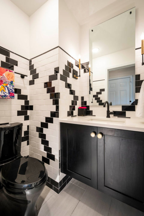"Fun Black and White Powder Room, custom wall tile patterns, unique wall tile layout, wall tile 72"" high, Unusual black and white tile pattern, wall tile patterns, Trinsic Single Lever Faucet by Delta in Black, Verticyl Rectangle Sink by Kohler, Persuasion toilet by Kohler in black, Livingston 1 light sconces by Elk, black and gold sconces, 3x6 Ice White and Black Glossy subway tile in unique zig zag pattern, black and white wall tile pattern, wall tile with pencil mold and wood trim, Elipse Pure White Quartz top, Custom Maple Floating Vanity with Shaker Door Style in Black Stain, Amerock Knobs in Golden Champagne Finish"