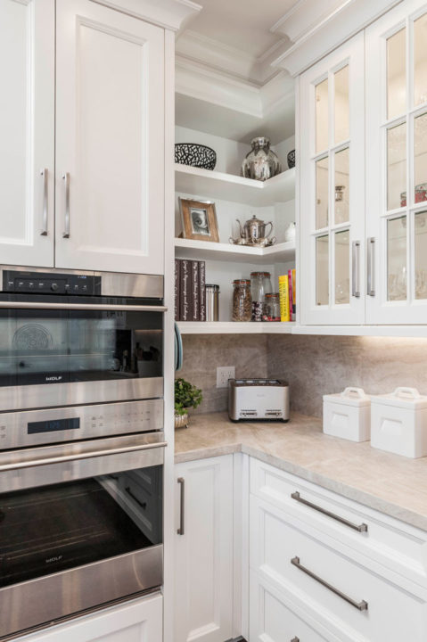 custom white painted, glass front cabinetry, inset panel cabinetry, Paras Stone tops, small ogee island top profile, white kitchen, undercounter lighting, Wolf appliances, wolf cooktop, custom cabinetry paneled refrigerator, microwave drawer,