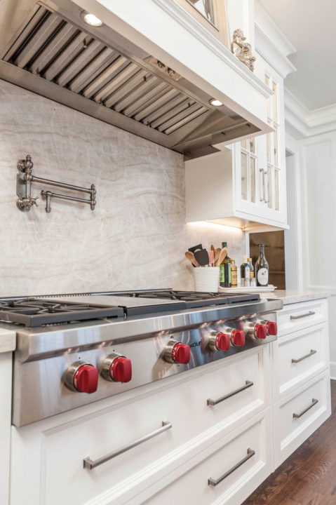 custom white painted, glass front cabinetry, inset panel cabinetry, Paras Stone tops, small ogee island top profile, white kitchen, undercounter lighting, Wolf appliances, wolf cooktop,