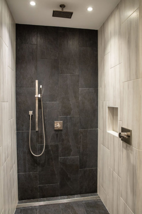 ADA shower with Vero Single handle faucets in master bath, vero Monitor Shower Trim and handheld shower, Gorge Dark Gray 12 x 24 Cliffside tile, vertical stack tile pattern, tile used as baseboard in bathroom, 12 x 24 Happy Floors Painted Stone White tile in vertical pattern, Delta Faucet plumbing