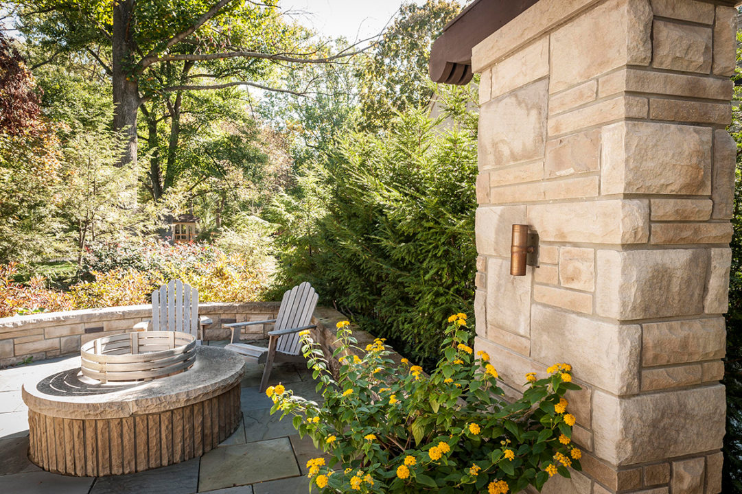 limestone columns in ashlar pattern, variegated split face limestone, blue stone patio, stone gas fire pit with seating area, fire pit with stainless fire ring, curved seating wall, dry stacked retaining wall