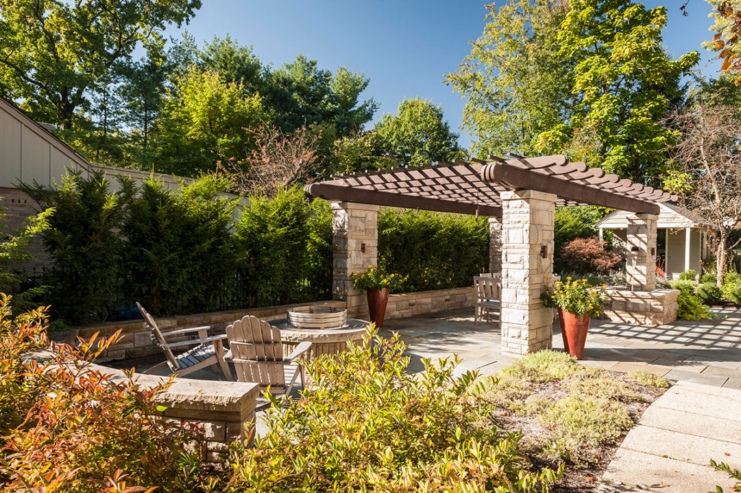 bracketed corbels, half round gutters, chain link downspouts, clap board siding, pergola with scalloped tail stacked limestone, limestone columns in ashlar pattern, variegated split face limestone, blue stone patio, water feature in limestone post, fountain in patio, copper waterspout, copper scupper water feature, stone gas fire pit with seating area, fire pit with stainless fire ring, curved seating wall, dry stacked retaining wall, limestone patio