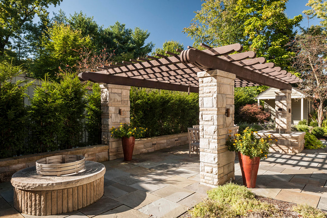 pergola with scalloped tails stacked limestone, limestone columns in ashlar pattern, variegated split face limestone, blue stone patio, water feature in limestone post, fountain in patio, copper waterspout, copper scupper water feature, stone gas fire pit with seating area, fire pit with stainless fire ring, dry stacked retaining wall, limestone patio