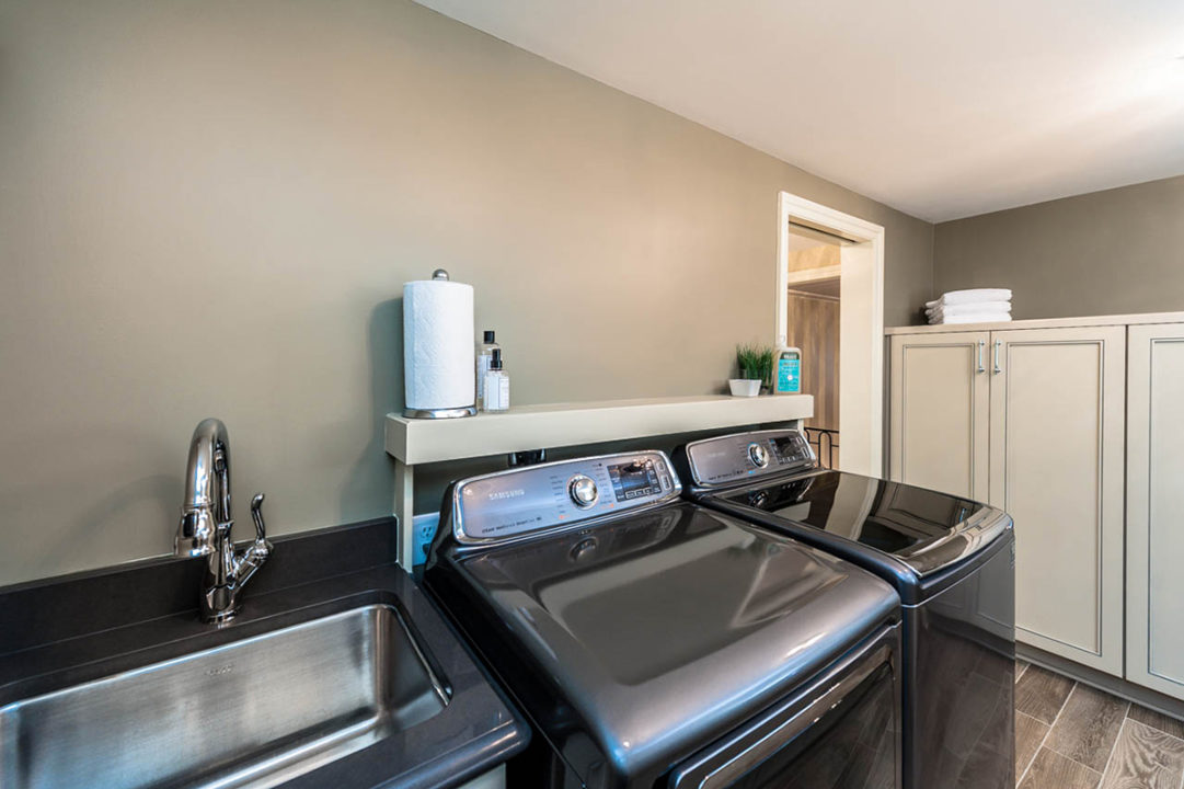 spacious laundry room, custom storage cabinetry, sink area