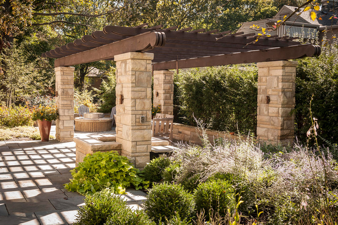 pergola with scalloped tails stacked limestone, limestone columns in ashlar pattern, variegated split face limestone, blue stone patio, stone gas fire pit with seating area, limestone patio