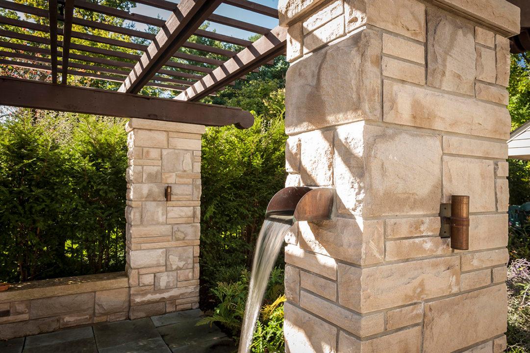 limestone columns in ashlar pattern, variegated split face limestone, water feature in limestone post, fountain in patio, copper waterspout, copper scupper water feature