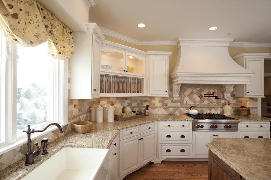 oil rubbed bronze cabinet hardware, custom white hood, bracketed feet on cabinets, curved kitchen island, white cabinetry, wood window valance, plate shelf, full overlay cabinets, wood hood with brackets