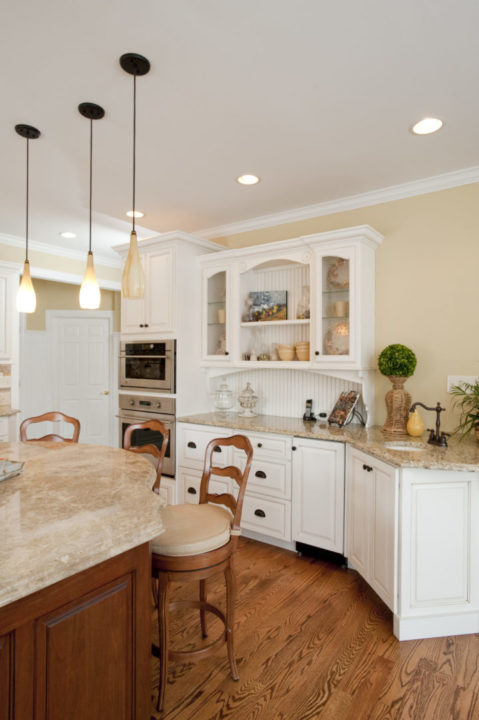 oil rubbed bronze cabinet hardware, vertical open shelves, curved kitchen island, white cabinetry, full overlay cabinets, bead board serving area