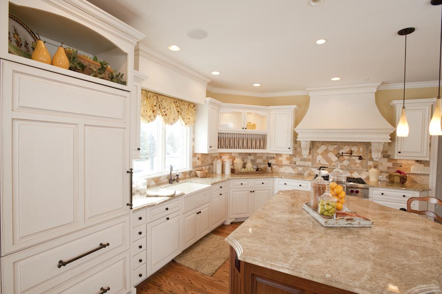 oil rubbed bronze cabinet hardware, custom white hood, vertical open shelves, bracketed feet on cabinets, curved kitchen island, white cabinetry, wood window valance, plate shelf, full overlay cabinets, wood hood with brackets