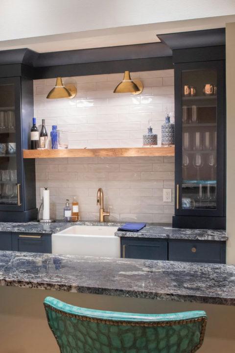 shaker style cabinets, library lights, floating wood shelf, tile backsplash, granite countertops, farmhouse sink