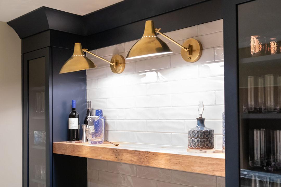 shaker style cabinets, library lights, floating wood shelf, tile backsplash