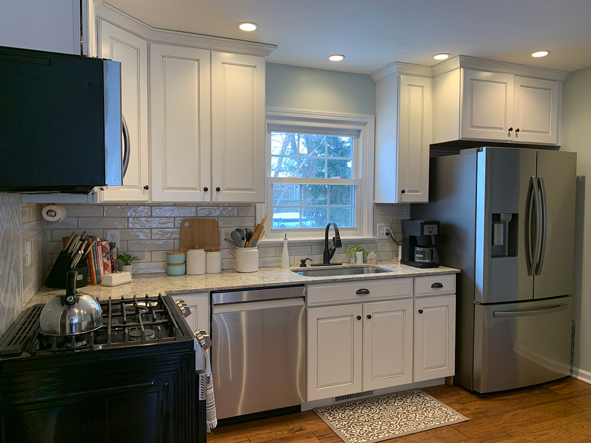traditional raised panel cabinets, raised panel cabinets, white and gray glazed cabinets, stainless steel appliances, herringbone pattern tile backsplash, butcher block countertop, quartz countertops, engineered floor, open dining room and kitchen