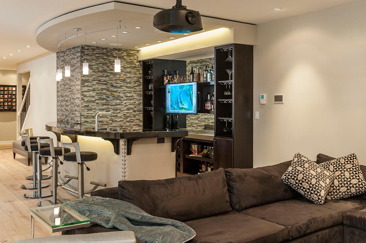 basement bar, lounge area, quartz counters, wood bar top, pendant lighting, mirrored backsplash, curved bar