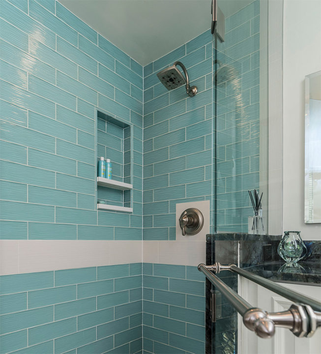 single shower head in teal glass tile shower