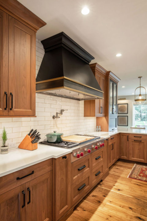 open concept kitchen, black and walnut kitchen, mixing stained and painted woods, kitchen of stained and painted wood, medium wood hardwoods, large sophisticated kitchen, entertainers space, transitional living spaces, transitional kitchen, gas range, black hood with gold trim