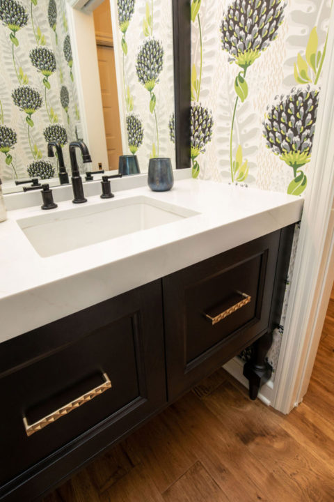 powder bath, black custom vanity, mitred quartz countertop, countertop to ceiling mirror, black and green floral wallpaper