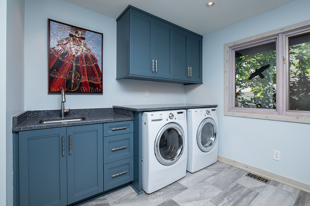 blue and white laundry, laundry with lots of cabinetry, folding area in laundry, bench in laundry, blue and gray laundry room, gorgeous laundry, creative laundry layout, ironing board in wall cabinet, fold down cabinet for iron, iron storage